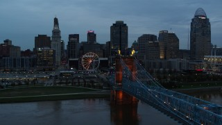 DX0001_003161 - 5.7K stock footage aerial video flyby city skyline and Ferris wheel at sunset, reveal bridge and Ohio River, Downtown Cincinnati, Ohio