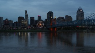 DX0001_003162 - 5.7K stock footage aerial video descend by Ohio River at sunset with view of bridge and skyline, Downtown Cincinnati, Ohio