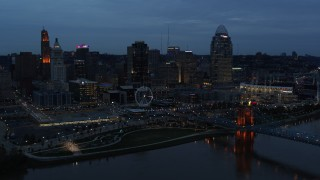 DX0001_003164 - 5.7K stock footage aerial video of the city skyline and bridge lit for twilight, seen from Ohio River, Downtown Cincinnati, Ohio