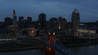 DX0001_003166 - 5.7K stock footage aerial video flyby city skyline and bridge lit for twilight, seen from Ohio River, Downtown Cincinnati, Ohio