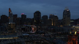 DX0001_003167 - 5.7K stock footage aerial video approach city skyline and Ferris wheel lit up at twilight, seen from Ohio River, Downtown Cincinnati, Ohio