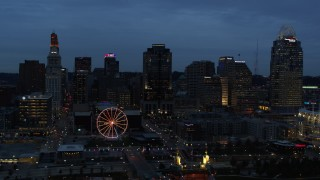 DX0001_003168 - 5.7K stock footage aerial video reverse view of city skyline and Ferris wheel lit up at twilight, reveal bridge and Ohio River, Downtown Cincinnati, Ohio