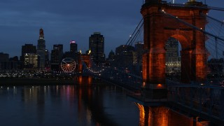 DX0001_003172 - 5.7K stock footage aerial video stationary view of city skyline behind Roebling Bridge lit up at twilight, seen from Ohio River, Downtown Cincinnati, Ohio