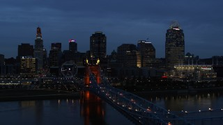 DX0001_003173 - 5.7K stock footage aerial video ascend from Roebling Bridge lit up at twilight, approach city skyline, Downtown Cincinnati, Ohio