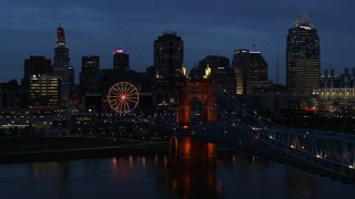 DX0001_003174 - 5.7K stock footage aerial video flyby Roebling Bridge lit up at twilight, and away from city skyline, Downtown Cincinnati, Ohio