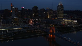 DX0001_003178 - 5.7K stock footage aerial video flying by lights of city skyline and bridge at twilight, seen from river, Downtown Cincinnati, Ohio