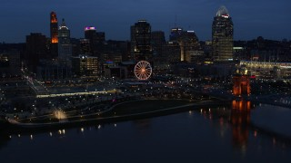 DX0001_003179 - 5.7K stock footage aerial video flying by lights of city skyline and bridge at twilight, seen from across river, Downtown Cincinnati, Ohio