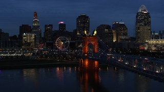 DX0001_003181 - 5.7K stock footage aerial video ascend from river by bridge to approach city skyline at twilight, Downtown Cincinnati, Ohio