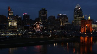 DX0001_003183 - 5.7K stock footage aerial video fly away from skyscraper and Ferris wheel at twilight, reveal the river and bridge, Downtown Cincinnati, Ohio