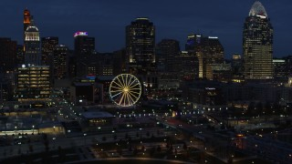 DX0001_003185 - 5.7K stock footage aerial video flying by Ferris wheel and skyscrapers at twilight, Downtown Cincinnati, Ohio
