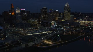 DX0001_003186 - 5.7K stock footage aerial video reverse view of Ferris wheel and skyscrapers at twilight, reveal river, Downtown Cincinnati, Ohio