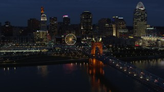 DX0001_003188 - 5.7K stock footage aerial video descend by the bridge with a view of the skyline across the river at twilight, Downtown Cincinnati, Ohio