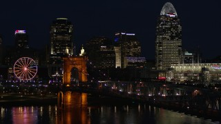 DX0001_003191 - 5.7K stock footage aerial video fly over Roebling Bridge at night to approach city skyline, Downtown Cincinnati, Ohio