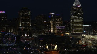 DX0001_003192 - 5.7K stock footage aerial video of flying by tall skyscrapers and Ferris wheel at night in Downtown Cincinnati, Ohio