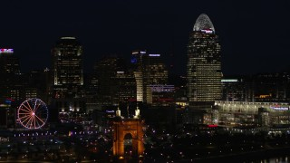 DX0001_003193 - 5.7K stock footage aerial video of passing by tall skyscrapers and Ferris wheel at night in Downtown Cincinnati, Ohio