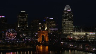 DX0001_003194 - 5.7K stock footage aerial video descend and pass bridge, tall skyscrapers and Ferris wheel at night in Downtown Cincinnati, Ohio