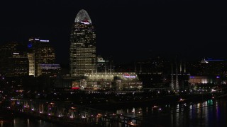 DX0001_003196 - 5.7K stock footage aerial video descend by tall skyscraper and the baseball stadium at night, reveal bridge, Downtown Cincinnati, Ohio