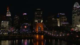 DX0001_003201 - 5.7K stock footage aerial video descend by Roebling Bridge at night with city skyline in background, Downtown Cincinnati, Ohio