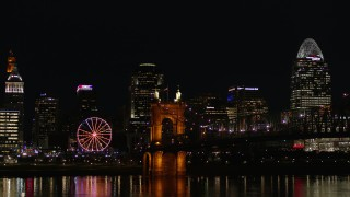 DX0001_003202 - 5.7K stock footage aerial video of the Roebling Bridge at night with city skyline in background, Downtown Cincinnati, Ohio