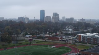 DX0001_003203 - 5.7K stock footage aerial video ascend from football field for view of the city skyline, Downtown Lexington, Kentucky