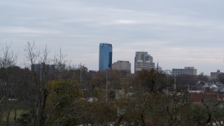 DX0001_003210 - 5.7K stock footage aerial video ascend from trees to reveal city's skyline, Downtown Lexington, Kentucky
