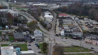 DX0001_003224 - 5.7K stock footage aerial video reverse view of a busy street and railroad tracks in industrial area in Lexington, Kentucky