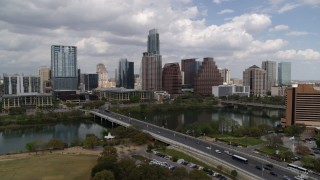 DX0002_102_001 - 5.7K stock footage aerial video of the city's skyline while flying by First Street Bridge and Lady Bird Lake, Downtown Austin, Texas