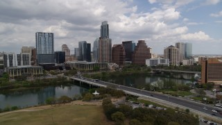 DX0002_102_004 - 5.7K stock footage aerial video slowly pass First Street Bridge and Lady Bird Lake with view of skyline, Downtown Austin, Texas