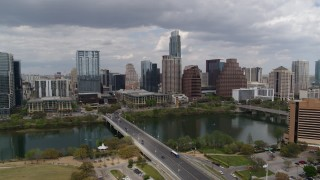DX0002_102_011 - 5.7K stock footage aerial video descend near First Street Bridge and Lady Bird Lake with view of skyline, Downtown Austin, Texas