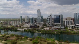 DX0002_102_013 - 5.7K stock footage aerial video of a reverse view of city skyscrapers across Lady Bird Lake, Downtown Austin, Texas
