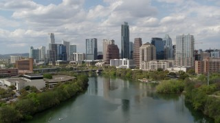 DX0002_102_020 - 5.7K stock footage aerial video of a reverse view of the city skyline while flying over Lady Bird Lake, Downtown Austin, Texas