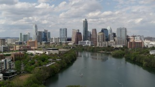 DX0002_102_024 - 5.7K stock footage aerial video descend toward Lady Bird Lake and focus on skyline of Downtown Austin, Texas