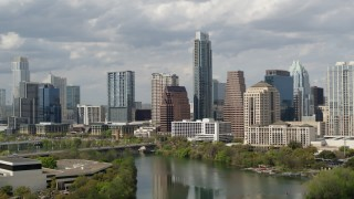 DX0002_103_001 - 5.7K stock footage aerial video ascend over Lady Bird Lake, approach skyscrapers in Downtown Austin, Texas