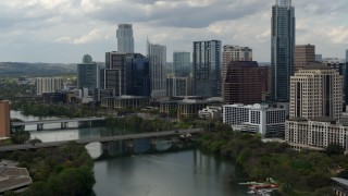 DX0002_103_012 - 5.7K stock footage aerial video follow Lady Bird Lake toward skyscrapers in Downtown Austin, Texas