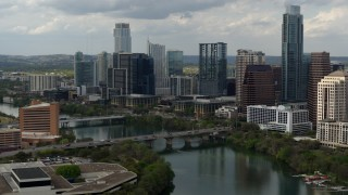 DX0002_103_013 - 5.7K stock footage aerial video fly away from bridge spanning Lady Bird Lake near skyscrapers in Downtown Austin, Texas