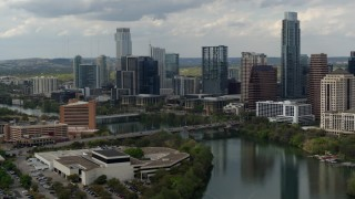 DX0002_103_014 - 5.7K stock footage aerial video fly away from bridge over Lady Bird Lake near waterfront skyscrapers in Downtown Austin, Texas