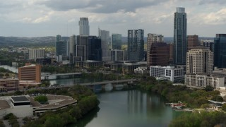 DX0002_103_015 - 5.7K stock footage aerial video approach and flyby bridge across Lady Bird Lake by waterfront skyscrapers in Downtown Austin, Texas