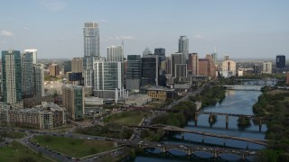 DX0002_104_003 - 5.7K stock footage aerial video a reverse view of skyscrapers and bridges spanning Lady Bird Lake, Downtown Austin, Texas