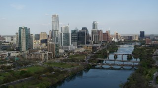 DX0002_104_004 - 5.7K stock footage aerial video descend by Lady Bird Lake with view of bridges and skyscrapers, Downtown Austin, Texas