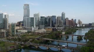 DX0002_104_013 - 5.7K stock footage aerial video fly away from towering skyscrapers and bridges over Lady Bird Lake, Downtown Austin, Texas