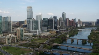 DX0002_104_015 - 5.7K stock footage aerial video passing towering skyscrapers by bridges over Lady Bird Lake, Downtown Austin, Texas