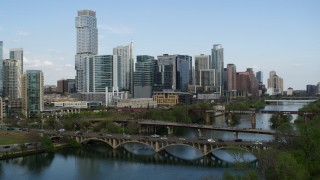 DX0002_104_016 - 5.7K stock footage aerial video descend bridges over Lady Bird Lake with view of skyscrapers, Downtown Austin, Texas