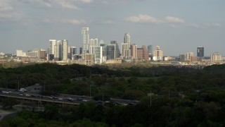 DX0002_104_017 - 5.7K stock footage aerial video ascend from hills for wide view of city skyline, Downtown Austin, Texas