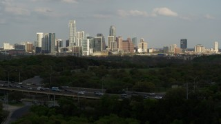 DX0002_104_023 - 5.7K stock footage aerial video ascend from green trees by freeway for wide view of city's towering skyline, Downtown Austin, Texas
