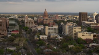DX0002_104_034 - 5.7K stock footage aerial video of passing by the Texas State Capitol building at sunset in Downtown Austin, Texas
