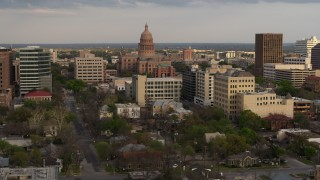 DX0002_104_035 - 5.7K stock footage aerial video of passing by the Texas State Capitol and office buildings at sunset in Downtown Austin, Texas