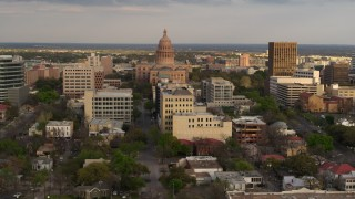 DX0002_104_037 - 5.7K stock footage aerial video flyby the Texas State Capitol behind office buildings at sunset in Downtown Austin, Texas
