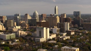 DX0002_104_040 - 5.7K stock footage aerial video reverse view and flyby of a courthouse and office buildings near skyscrapers at sunset in Downtown Austin, Texas