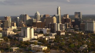 DX0002_104_041 - 5.7K stock footage aerial video a slow approach to a courthouse and office buildings near skyscrapers at sunset in Downtown Austin, Texas