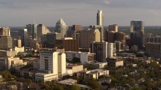 DX0002_104_042 - 5.7K stock footage aerial video of passing a courthouse and office buildings near skyscrapers at sunset in Downtown Austin, Texas